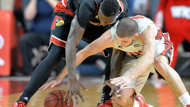 Louisville's Terry Rozier, lefdt, battles Western Kentucky's Chris Harrison-Docks for a loose ball during the first half of an NCAA college basketball game Saturday, Dec. 20, 2014, in Bowling Green, Ky. (AP Photo/Timothy D. Easley)