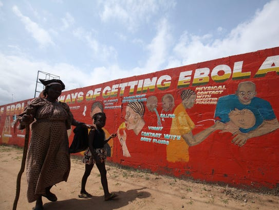 A child with her blind mother walks past a a mural