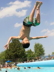 Emmett Meissner, of Chili, does a flip off the board at Hefko Pool in Marshfield in this 2011 file photo.