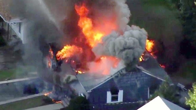 FILE-- In this Sept. 13, 2018 file image taken from video provided by WCVB in Boston, flames consume a home of Lawrence, Mass. police officer Ivan Soto in Lawrence, Mass, a suburb of Boston. Columbia Gas of Massachusetts was ordered Tuesday, June 23, 2020, to pay a $53 million criminal fine for causing a series of natural gas explosions in Lawrence and nearby towns that killed one person and damaged dozens of homes. The company was sentenced more than three months after the it pleaded guilty in federal court to causing the blasts.