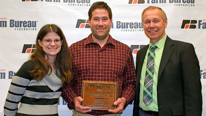 Lafayette County farmers, Chad and Katrina Gleason, were selected as the winners of the Wisconsin Farm Bureau Federation Young Farmer and Agriculturist Achievement Award at the organization's 98th Annual Meeting. They are pictured Wisconsin Farm Bureau Federation President Jim Holte (right).