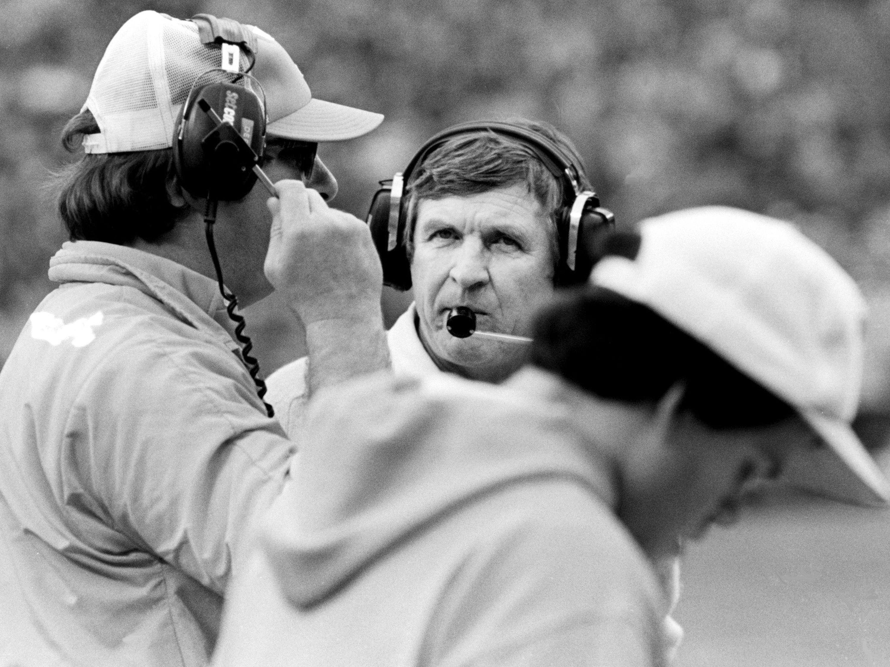 Tennessee head coach Johnny Majors, center, checks with assistant coach Bill Shaw, left, on the sidelines in their Peach Bowl game with Iowa in Atlanta Dec. 31, 1982.
