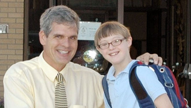 Tim Reilly pictured with a Saint Ignatius Loyola School student in 2010. Reilly was named president of St. Xavier High School Friday.