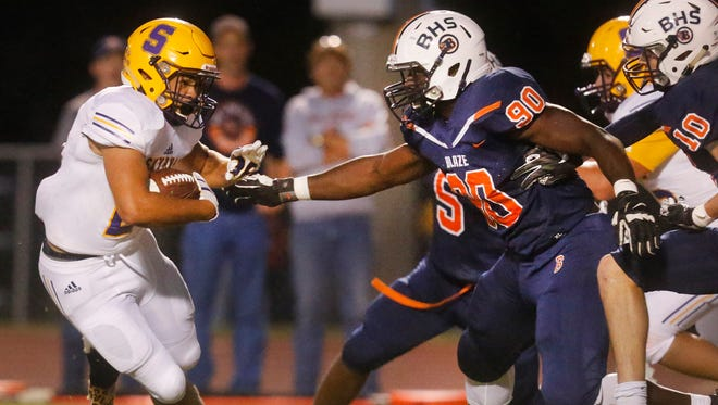 Smyrna's Blake Watkins (21) runs the ball as Blackman's Ben Kalu (90) and Matthew Hall (10) move in for the tackle during the game, on Friday, Sept. 8, 2017, at Blackman.