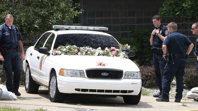 IMPD officer Perry Renn was shot and killed July 5, 2014, behind a home near 34th Street and Forest Manor Avenue, Indianapolis. Here, IMPD officers on July 6 look at a memorial featuring Renn's patrol car at the IMPD North District headquarters, 3120 E. 30th St.