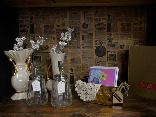 Honey jars, a book, vases and other items adorn a shelf in a bookcase papered with an antique newspaper background.
