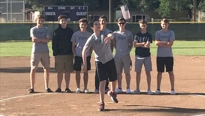 Colton Rickard throws out the first pitch of Friday's softball game with the support of his teammates on the Redding Rampage soccer team.