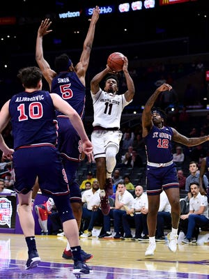 Shannon Evans II #11 of the Arizona State Sun Devils attempts a jumper between Bryan Trimble Jr. #12 and Justin Simon #5 of the St. John's Red Storm during the Basketball Hall of Fame Classic at Staples Center on December 8, 2017 in Los Angeles, California.