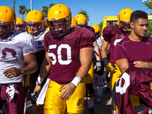 Arizona State's Kweishi Brown (10), left, Nick Kelly (50, and D.J. Foster, right, join other Sun Devils arriving for practice on Thursday, Aug. 7, 2014, at the Bill Kajikawa Football Practice Field in Tempe. The team's first game is in three weeks (8/28), against Weber State at Sun Devil Stadium.