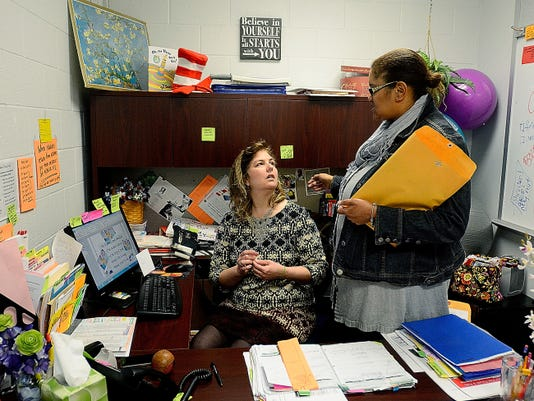 Dawn Squire, seated in her office at McKinley K-8, shares ideas on a poster design with Karen Fitch, who has a job similar to Squire's at William Penn High School. While her official title is family involvement coordinator, Squire's duties include orienting new students, picking up and dropping off students and tour guide.
