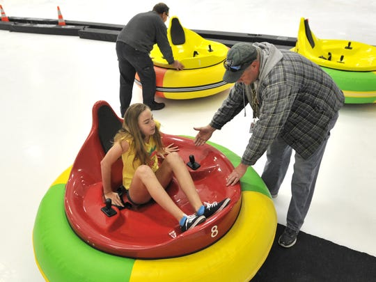 Juliana Sites, 9, of Frederica, is helped out of her bumper car in Harrington last weekend. A 5-minute ride costs $5.