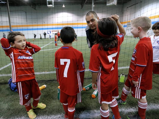FC Dallas players confer with their coach during an