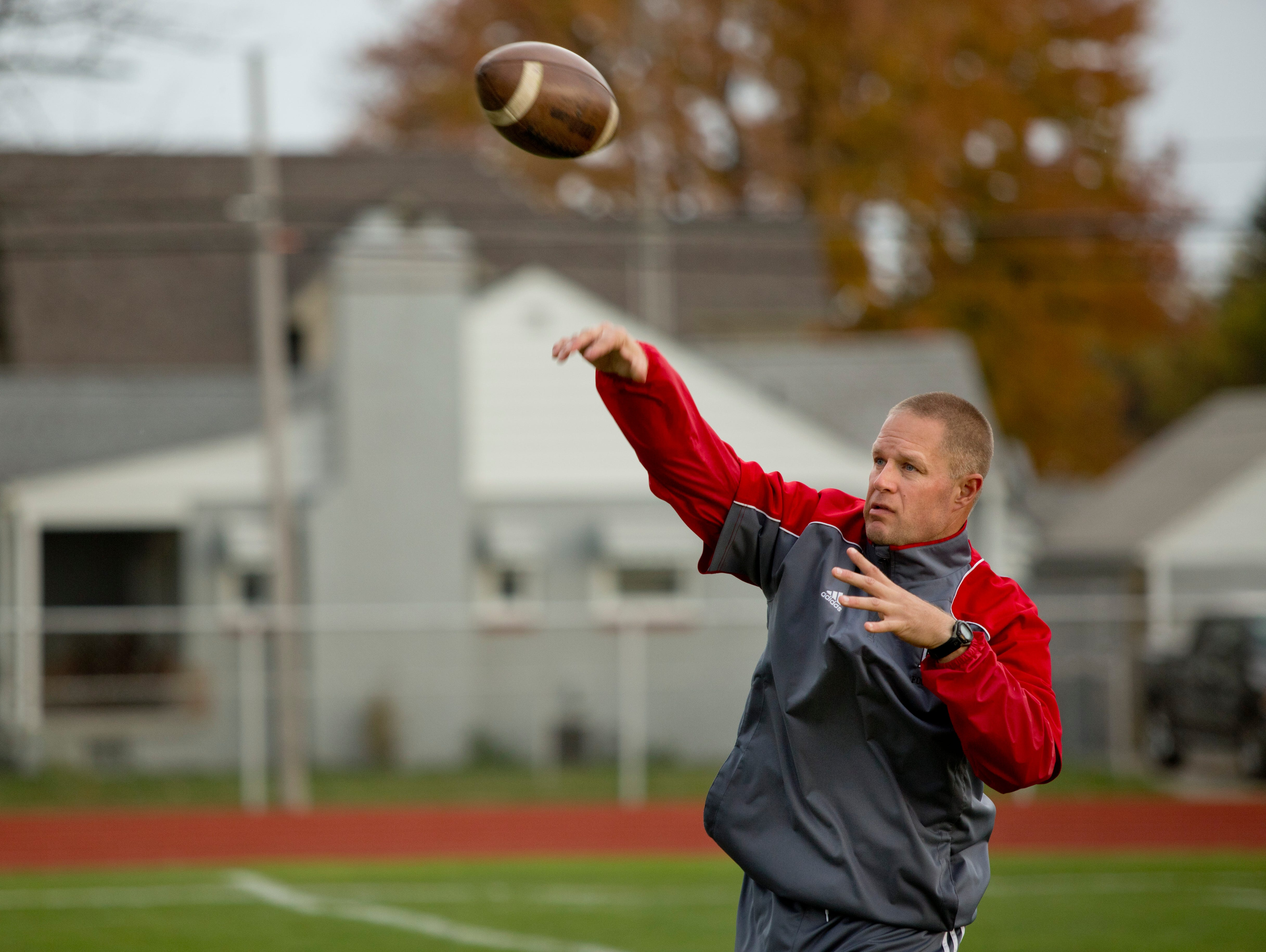 Port Huron coach Ryan Mullins throws a pass during practice Tuesday, October 20, 2015 at Port Huron High School.