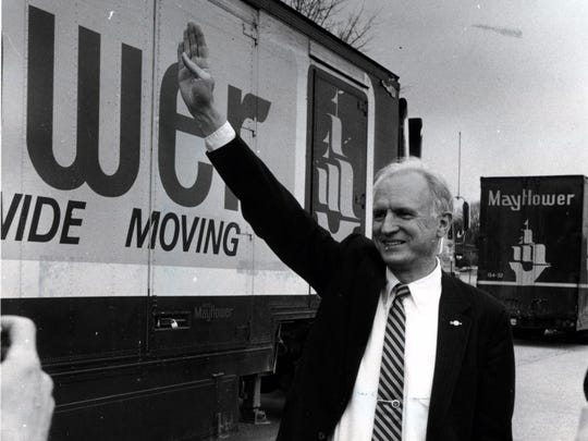 Indianapolis Mayor William 'Bill' Hudnut poses by Mayflower moving vans filled with Indianapolis Colts possessions that just arrived from Baltimore at Fall Creek Elementary School, site of the the temporary facility on March, 1984.