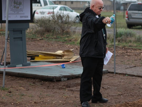 Bishop Michael Pfeifer pours water he blessed over the site of the new detox center during the Alcohol & Drug Abuse Council of the Concho Valley groundbreaking ceremony in 2016.