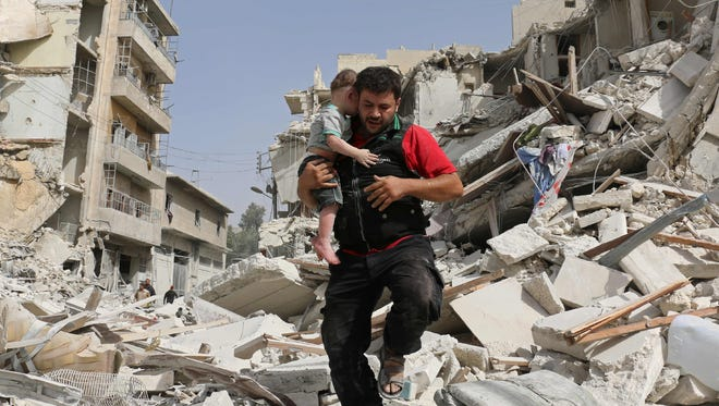 A Syrian man carries a baby after removing him from the rubble of a destroyed building following a reported airstrike in the Qatarji neighborhood of the northern city of Aleppo, Syria, on Sept. 21, 2016.