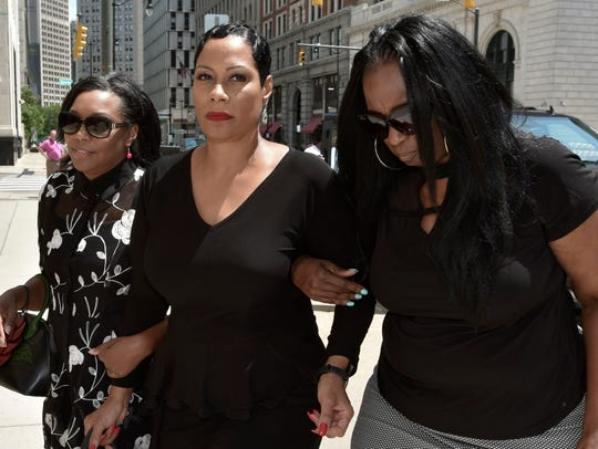 Monica Morgan-Holiefield, center, is escorted by two unidentified women as she enters the federal courthouse in downtown Detroit Friday for her sentencing hearing in July 2018.