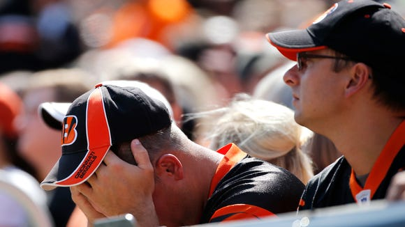 A Bengals fan covers his face after the Bengals Andy Dalton throws his second interception in the first half at Paul Brown Stadium Sunday September 10, 2017.