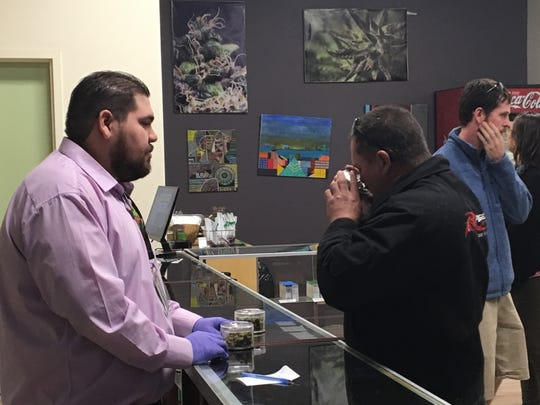 Desert Hot Springs resident Corey Banker (right) tests a product at Green Pearl Organics in Desert Hot Springs. Marijuana sales became legal in California Monday and shops across the Coachella Valley attracted customers.