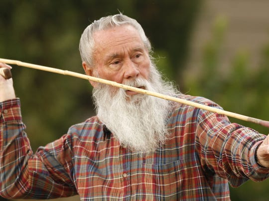 Jim Ray aims at his target with an atlatl during a
