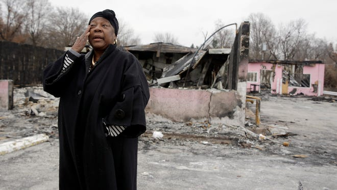 In this Dec. 9, 2014, photo, Juanita Morris wipes her eye as she stands outside the remains of her burned-out business in Dellwood, Mo. On the morning of Nov. 24, Juanita's Fashions R Boutique opened for business as usual. By dawn the next day, it was a burned-out shell following a night of rioting after the announcement that a grand jury would not indict a white police officer in the shooting death of Michael Brown. (AP Photo/Jeff Roberson)