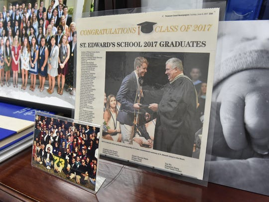 A newspaper photo of Bruce Wachter handing out diplomas is seen with other memorabilia of his 45-year career at St. Edward's School, on a desk in his office. Surrounding photos (left) are of the current seniors commissioning ceremony, (bottom) Wachter holding the '73' for his William & Mary 25th reunion class photo, and (right) his then 3-day-old granddaughter Laura's hand holding his thumb. CQ: Bruce Wachter