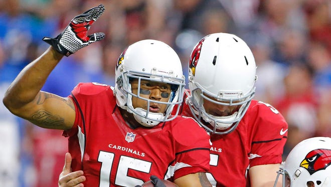 Cardinals wide receiver Michael Floyd (15) is greeted by quarterback Drew Stanton (5) following his first touchdown against the Detroit Lions in the first quarter of their NFL game Sunday, Nov. 16, 2014 in Glendale.
