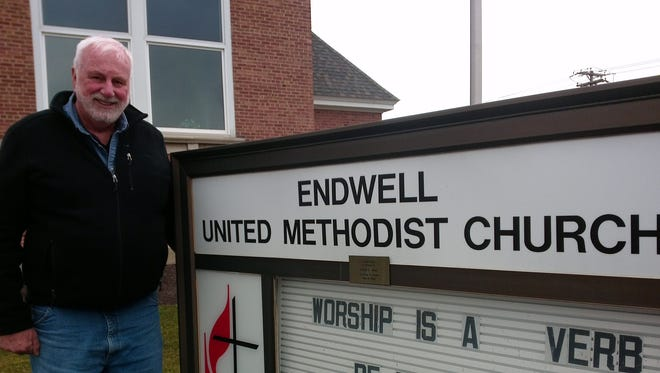 Dave Alexander,  Facilities Manager and Assistant for Outreach Ministries,  by Endwell United Methodist Church sign.
