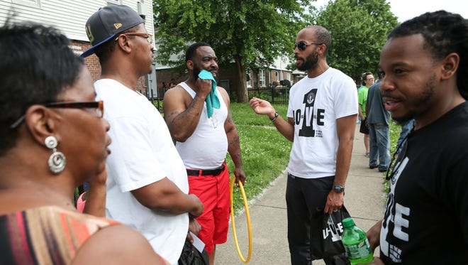 Brandyn Bailey, from right, and Rashaad Abdur-Rahman with the Office for Safe and Healthy Neighborhoods talk with Frank Irvin, Clarence Taylor and other Beecher Terrace housing complex residents before a walk through the neighborhood in May 2016