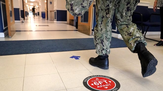 A social distancing sign is seen on the floor as a midshipman walks to class at Luce Hall at the U.S. Naval Academy, Monday, Aug. 24, 2020, in Annapolis, Md.