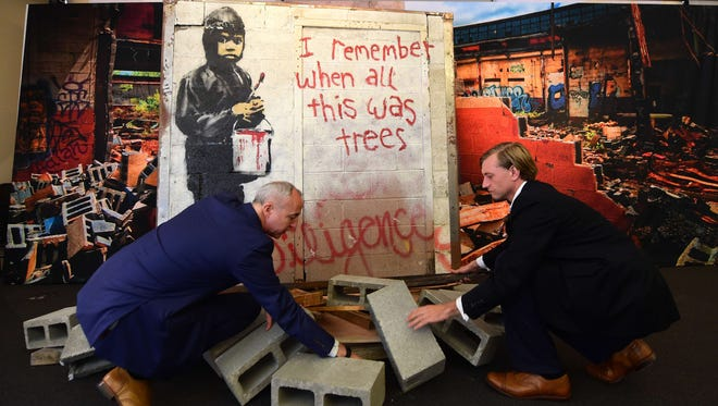 "Martin Nolan, left, and Michael Doyle of Julien's Auctions prepare a display of the artist Banksy's ""I Remember When All This Was Trees"" on Sept. 23, 2015 at Julien's Auctions in Beverly Hills, Calif., ahead of the ""Street Art and Contemporary Art"" auction on Sept. 30 and Oct. 1."