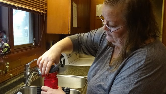Rena Keckler prepares a water bottle before Greg Miley, who is physically disabled, takes his medications. Keckler works at a house on South Seffner Avenue, where she helps its residents with daily tasks such as cooking, bathing and going to bed.
