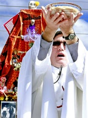 Father Ricardo Bauza holds up the host in November