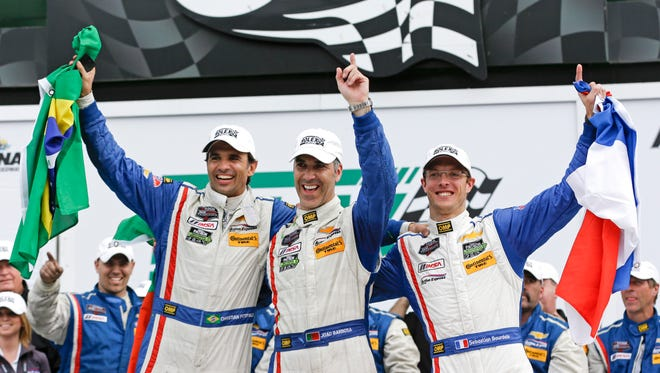 The Action Express team, from left, Christian Fittipaldi, Joao Barbosa and Sebastien Bourdais, celebrate in victory lane after winning the Rolex 24 at Daytona.