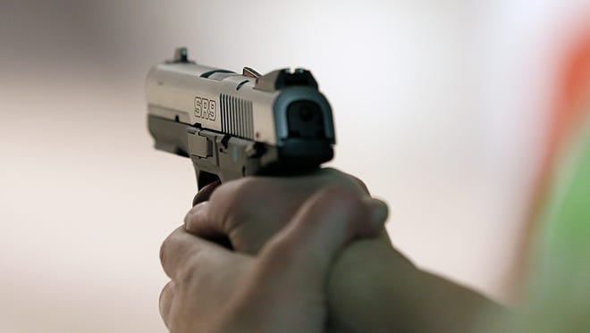 """A women fires a handgun at the """"Get Some"""" Guns & Ammo shooting range."""