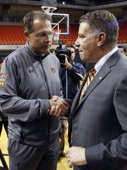 Auburn football coach Gus Malzahn, left, greets Bruce