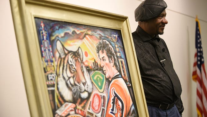 Farmington Hills artist Curtis Lewis poses for a photo with his painting dedicated to Mike Ilitch.