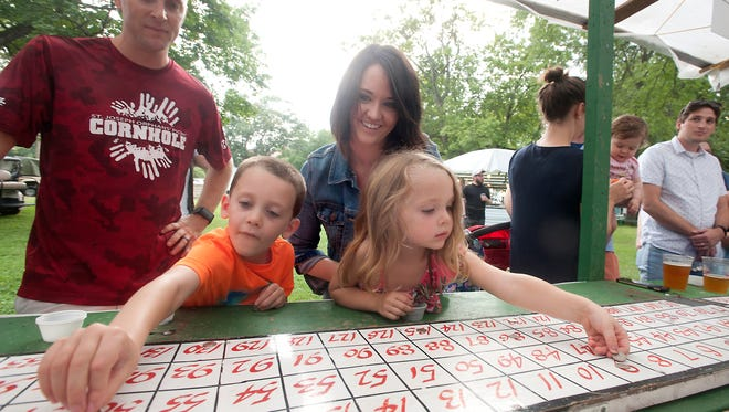 """Brandon and Jamie Estenfelder of Owl Creek watch as their children, Harrison, 5, and Charlotte, 3, place a dime each on the cake wheel board at St, Joseph Children's Home annual picnic. Jamie said she grew up coming to the event. """"It's a fun way to support the cause,"""" she said.  Aug. 11, 2017"""