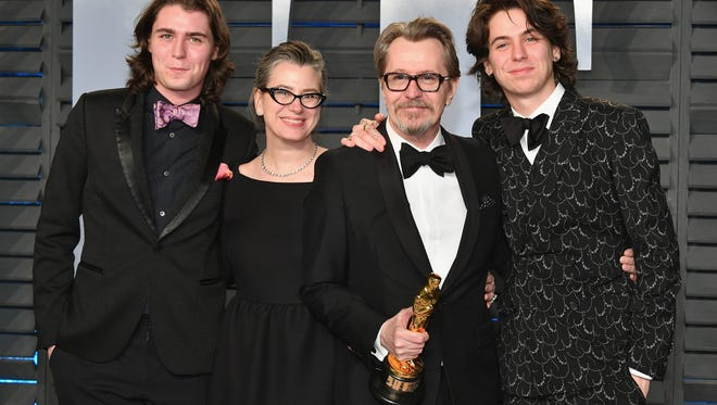Newly-minted Oscar winner Gary Oldman was surrounded by his family at the 'Vanity Fair' after-party.  (From left: Son Gulliver, wife Gisele Schmidt,  Oldman and son Charlie)