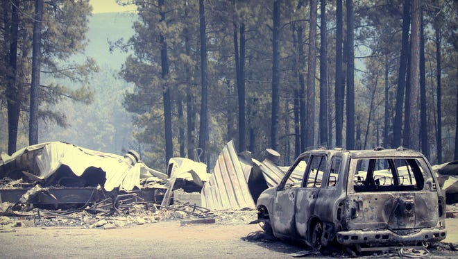 A burned-out vehicle sits next to a structure destroyed in the 290 acre wildfire near Timberon, N.M. Thursday. It's one of 16 vehicles destroyed in the blaze. An estimated 31 were also destroyed in the fire that started Wednesday afternoon.
