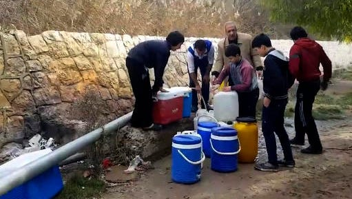 This frame grab from video provided By Yomyat Kzefeh Hawen Fi Dimashq (Diary of a Mortar Shell in Damascus), a Damascus-based media outlet that is consistent with independent AP reporting, shows Syrian residents filling up buckets and gallons of spring water from a pipe on the side of the road, in Damascus, Syria. Water supplies to Damascus have been largely cut off for nearly two weeks because of fighting between pro-government forces and rebels for control of the main tributary, forcing millions in the Syrian capital to scramble for enough to drink and wash with. The cut-off is a major challenge to the government's effort throughout the nearly 6-year-old civil war to keep the capital as insulated as possible from the effects of the conflict tearing apart much of the country.