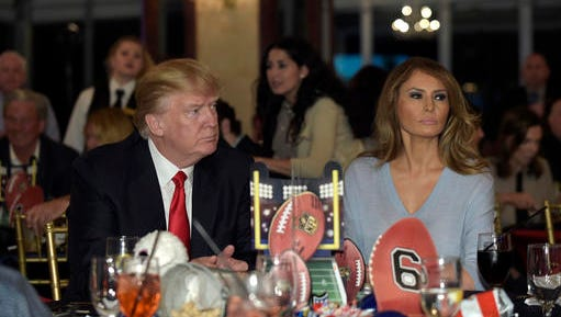 "FILE - In this Feb. 5, 2017 file photo, President Donald Trump and first lady Melania Trump watch the Super Bowl at a party at Trump International Golf Club in West Palm Beach, Fla. First lady Melania Trump isn't living in the White House and has said little about what she intends to do with her prominent position. But in new court documents, her lawyers argue that the ""multi-year term"" during which she ""is one of the most photographed women in the world"" should mean millions of dollars for her personal brand.  (AP Photo/Susan Walsh, File)"