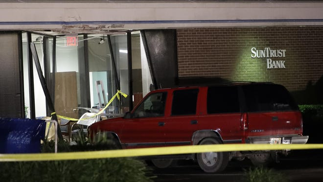 A red SUV is seen parked outside the damaged SunTrust bank early Jan. 24, 2019, in Sebring, Fla. Authorities say five customers were shot and killed at the bank on Wednesday.