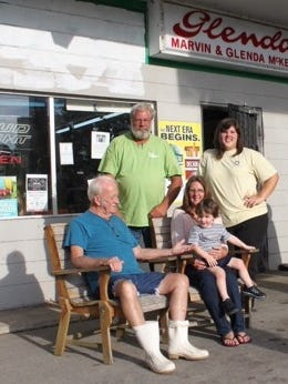 The Mckenzie family sits in front of Glenda's Country Store, one of the oldest local, family-owned businesses before it closed down last week.