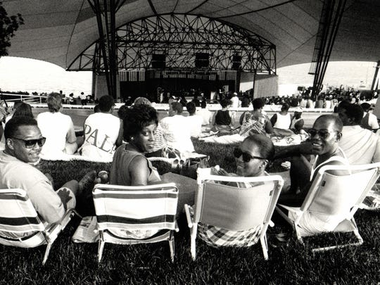 Concertgoers stake out spots on the lawn at Chene Park awaiting performances by comedian Sinbad and group Calloway in July 1990.