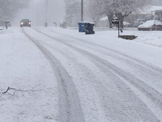A car drives with caution down a snow-covered road