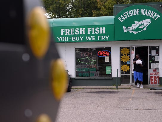 A customer walks out with his food at Eastside Fish