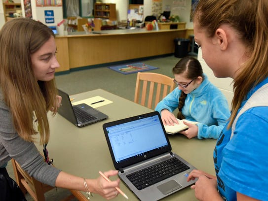 Tammy Lee, left, school counselor, helps students during