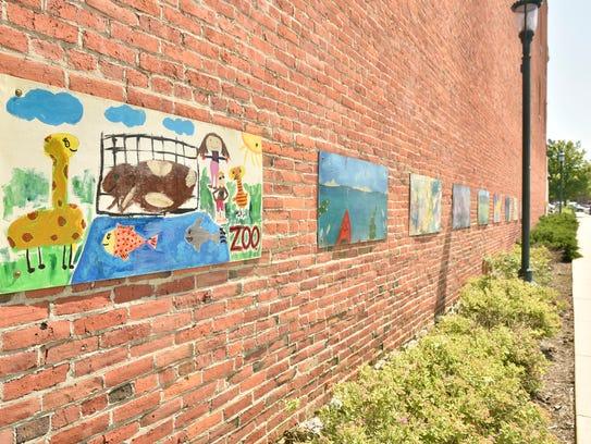 Art by local artist hangs on buildings in Downtown
