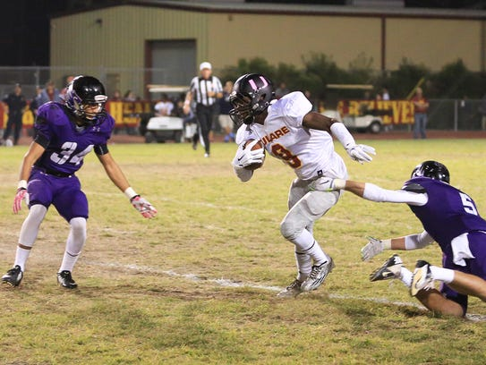 Tulare Union's Emoryie Edwards (9) rushes between Mission